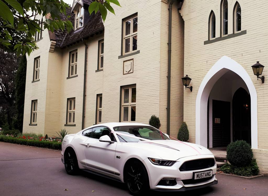 Image of 2018 white Ford Mustang outside the front of the Glen-Yr-Afon