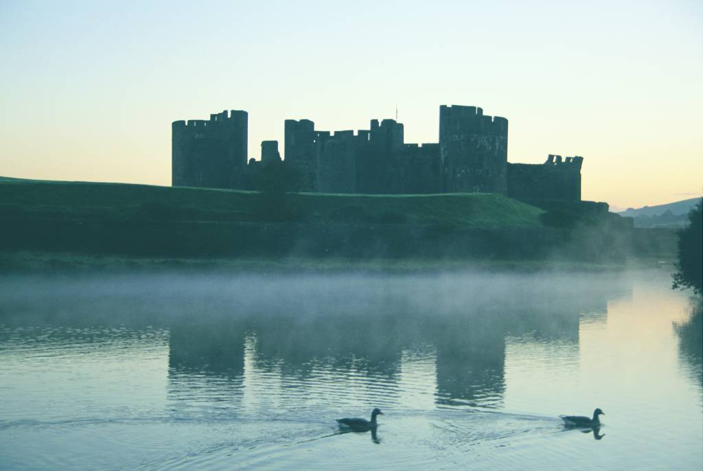A view over the lake surrounding Caerphilly Castle on a misty morning.© Crown copyright 2018 (Visit Wales)
