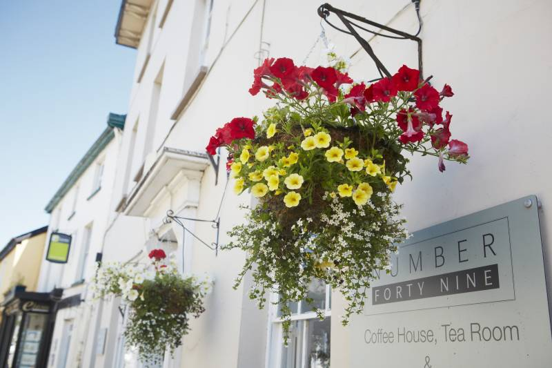 Image of lovely hanging baskets outside one of Usks local coffee shops. ©  Visit Monmouthshire